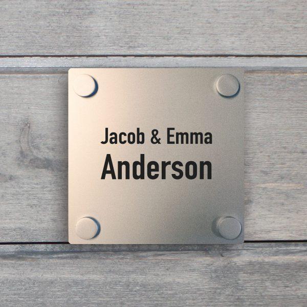 Bilde av et kvadratisk dørskilt i aluminium på en grå vegg.