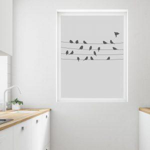 Kjøkken med fokus på vinduet som er foliert med frost. Frosten har illustrasjoner av fugler som sitter på tråer.