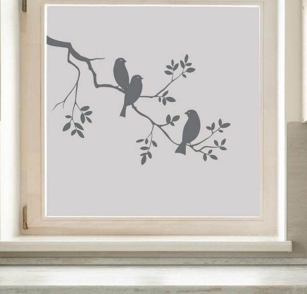 Vindu med frostet vindusfolie. Folien har et fuglemotiv. Tre små fugler sitter på en grein.