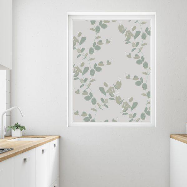Bilde av et kjøkken. Fokus på vindu med frostet vindusfolie. Motivet på vindusfolien er grønne blader.