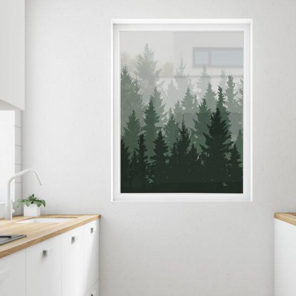 Bilde av et kjøkken med fokus på kjøkkenvinduet. Vinduet er dekorert med frostfolie. Folien har et bilde av granskog og skyggete tretopper.