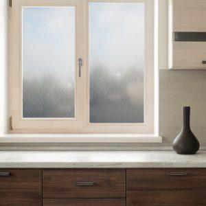 Miljøbilde av et kjøkken. Utsnitt av en kjøkkenbenk og et vindu. Vinduet er foliert med frostet vindusfolie. Folien har kvadratisk mønster.