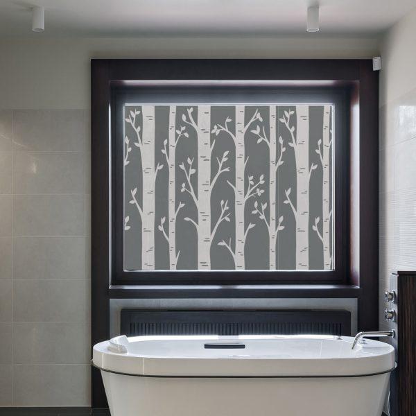 Bilde av et bad. Fokus på vinduet som er dekorert med en vindusfolie. Vindusfolien har illustrerte bjørketrær.