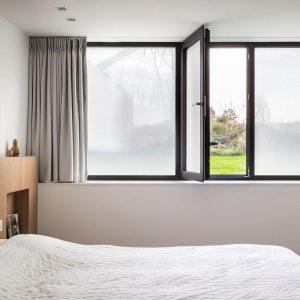 Bilde av et soverom. Vinduet er foliert med tekstil vindusfolie i fargen kalk.