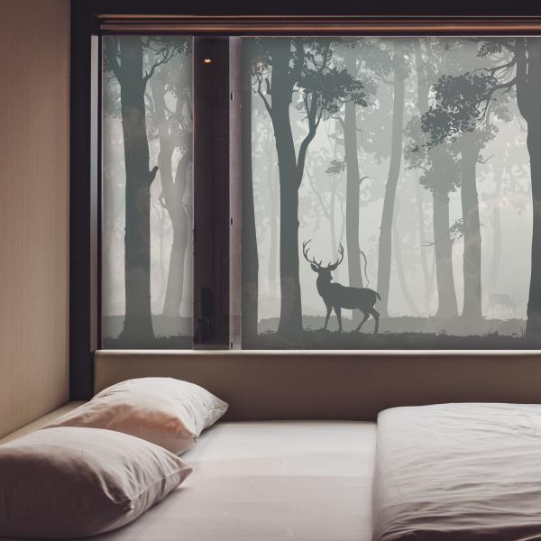 Utsnitt av et soverom. Et stort frostet vindu. Motivet er av en skog med et rådyr.