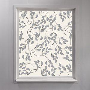 Bilde av et vindu med frostet vindusfolie. Vindusfolien har illustrerte blader på seg.