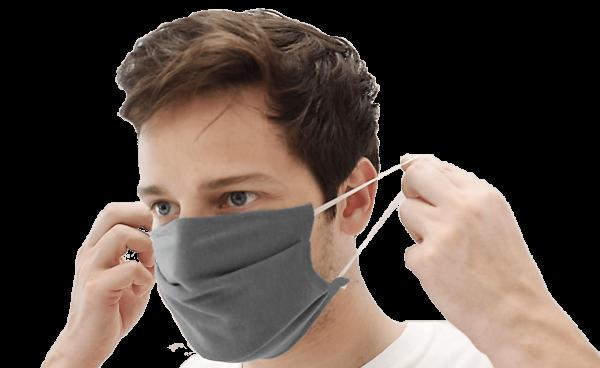 Mann som har på seg grått tøy munnbind.