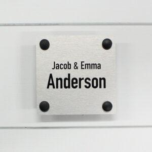 dørskilt i børstet aluminium med festeknotter i sort aluminium og sort tekst